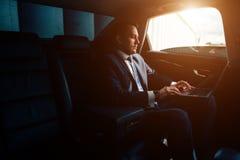 Homem de negócios considerável que fala com o telefone que senta-se com o portátil no assento traseiro do carro imagens de stock royalty free