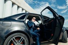 Homem de negócios considerável que fala com o telefone que senta-se com o portátil no assento traseiro do carro fotos de stock