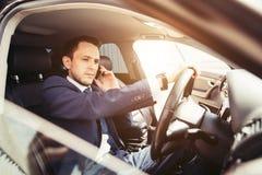 Homem de negócios considerável que fala com o telefone que senta-se com o portátil no assento traseiro do carro fotografia de stock