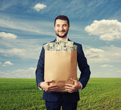Homem de negócios considerável que guarda o saco de papel com dinheiro Foto de Stock