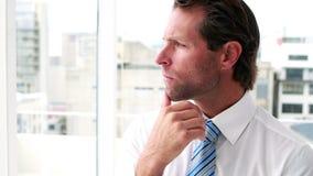 Homem de negócios considerável que pensa e que olha para fora a janela video estoque