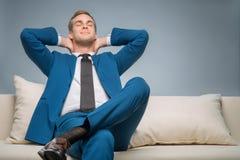 Homem de negócios considerável que relaxa no sofá imagem de stock