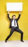 Homem de negócios considerável que tenta levantar acima a placa fotos de stock royalty free