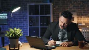 Homem de negócios considerável que trabalha com o portátil na noite na escrita do escritório no caderno vídeos de arquivo