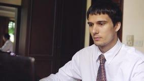 Homem de negócios considerável que trabalha em um escritório 3840x2160 filme
