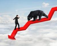Homem de negócios contra o urso na linha de tendência descendente da seta com céu imagens de stock royalty free