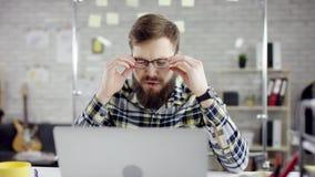 Homem de negócios cuidadoso produtivo que inclina o trabalho de escritório para trás de terminação no portátil, gerente eficaz sa filme