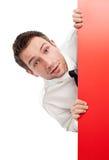 Homem de negócios curioso atrás do quadro de avisos vermelho Fotografia de Stock Royalty Free