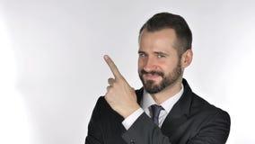 Homem de negócios da barba que aponta no lado, fundo branco filme