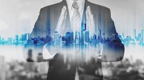 Homem de negócios da exposição dobro que guarda o holograma azul da cidade, tecnologia do negócio dos bens imobiliários fotos de stock royalty free