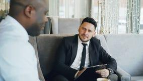 Homem de negócios da hora que tem a entrevista de trabalho com homem afro-americano e que olha sua aplicação do resumo no café mo vídeos de arquivo