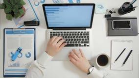 Homem de negócios da vista superior que trabalha no portátil com gráficos e cartas na mesa de escritório filme