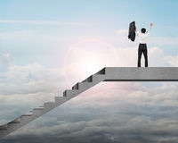 Homem de negócios da vista traseira que cheering sobre escadas com luz solar fotos de stock royalty free