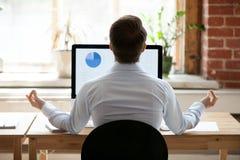 Homem de negócios da vista traseira que senta-se na mesa oposto ao PC que faz a ioga foto de stock royalty free