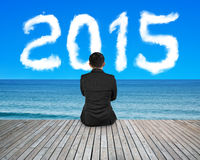 Homem de negócios da vista traseira que senta-se no assoalho de madeira com 2015 nuvens Imagens de Stock Royalty Free