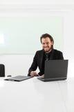 Homem de negócios de cabelos compridos que senta-se em uma sala de direção Imagem de Stock
