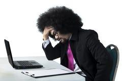 Homem de negócios de Dizzy Afro que trabalha com portátil imagens de stock