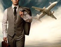 Homem de negócios de encontro ao plano do vôo imagem de stock