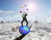 Homem de negócios de mnanipulação que está na bola dos símbolos que equilibra no fio Fotografia de Stock Royalty Free