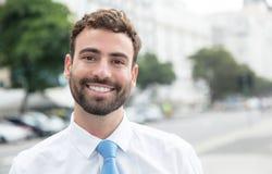 Homem de negócios de riso com barba e laço azul na cidade Fotografia de Stock