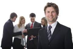 Homem de negócios de sorriso com colegas Imagens de Stock Royalty Free