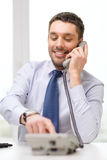 Homem de negócios de sorriso com número discado do telefone Imagens de Stock