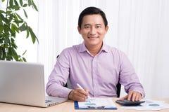 Homem de negócios de sorriso em sua mesa com portátil e originais no seu Fotos de Stock