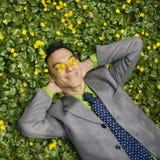 Homem de negócios de sorriso na correcção de programa da flor Imagens de Stock