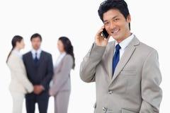 Homem de negócios de sorriso no telemóvel e na equipe atrás dele Fotos de Stock