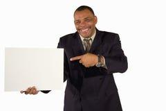 Homem de negócios de sorriso que aponta em uma placa do retrato Fotografia de Stock