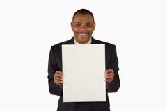 Homem de negócios de sorriso que apresenta uma placa do retrato Foto de Stock Royalty Free