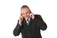 Homem de negócios de sorriso que convida dois telefones Fotografia de Stock