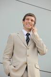 Homem de negócios de sorriso que fala em um telefone móvel Fotografia de Stock Royalty Free