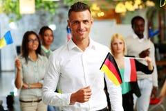 Homem de negócios de sorriso que guarda a bandeira de Alemanha Fotografia de Stock Royalty Free