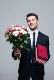 Homem de negócios de sorriso que guarda flores e caixa de presente Fotos de Stock