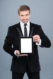 Homem de negócios de sorriso que guarda o PC digital da tabuleta com tela vazia Imagens de Stock Royalty Free