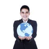 Homem de negócios de sorriso que guarda um globo Foto de Stock
