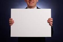 Homem de negócios de sorriso que prende um cartão em branco grande Fotos de Stock Royalty Free