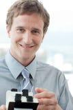 Homem de negócios de sorriso que prende um suporte do cartão Imagem de Stock