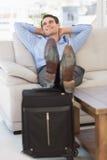 Homem de negócios de sorriso que relaxa no sofá com pés acima na mala de viagem imagem de stock royalty free