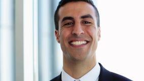 Homem de negócios de sorriso que toca em seu cabelo no escritório video estoque