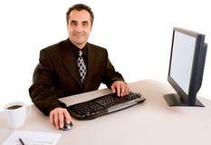 Homem de negócios de sorriso que trabalha em sua mesa Fotos de Stock Royalty Free