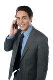Homem de negócios de sorriso que usa um telemóvel foto de stock royalty free