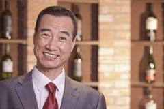 Homem de negócios de sorriso Standing por garrafas de vinho Imagens de Stock Royalty Free