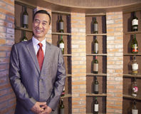 Homem de negócios de sorriso Standing por garrafas de vinho Fotografia de Stock Royalty Free