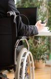 Homem de negócios deficiente que texting durante o trabalho fotografia de stock royalty free