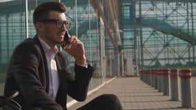 Homem de negócios denominado urbano que fala no smartphone ao sentar-se no aeroporto e ao esperar um voo Jovens ocasionais vídeos de arquivo