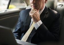 Homem de negócios dentro de um carro que trabalha em seu portátil imagens de stock royalty free