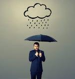 Homem de negócios desagradado com guarda-chuva fotografia de stock royalty free