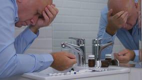 Homem de negócios desapontado Image no banheiro com comprimidos e drogas no dissipador fotografia de stock royalty free